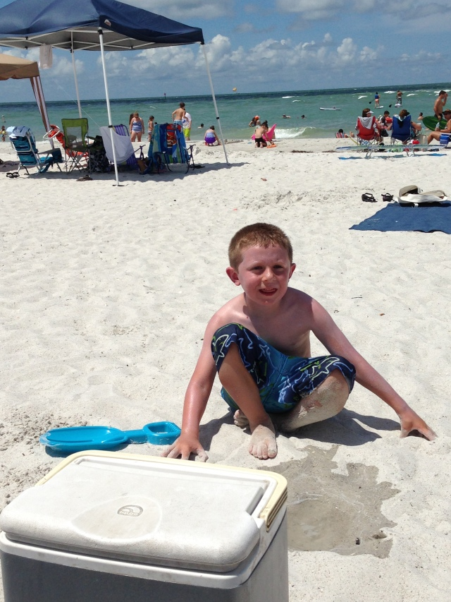 "First day on the beach.  Brayden was in love!  Though, I had to bribe him to smile ""normal"" for this picture!"
